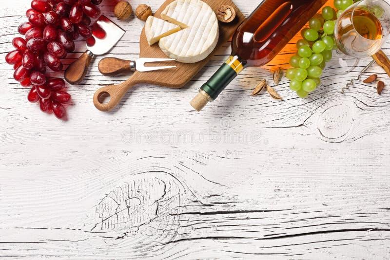 Flaska f?r vitt vin, druva, ost och vinglas p? det vita tr?br?det royaltyfri bild
