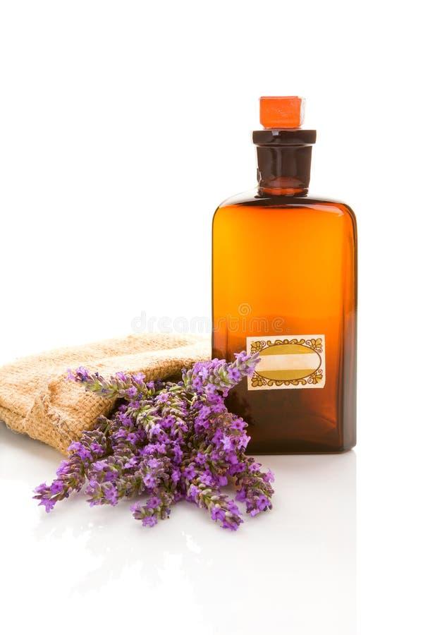 Flaska med aromolja- och lavendelblommor som isoleras på vit Ar fotografering för bildbyråer