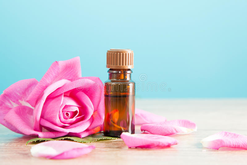 Flaska med den aromatiska olja- och rosa färgrosen arkivfoton