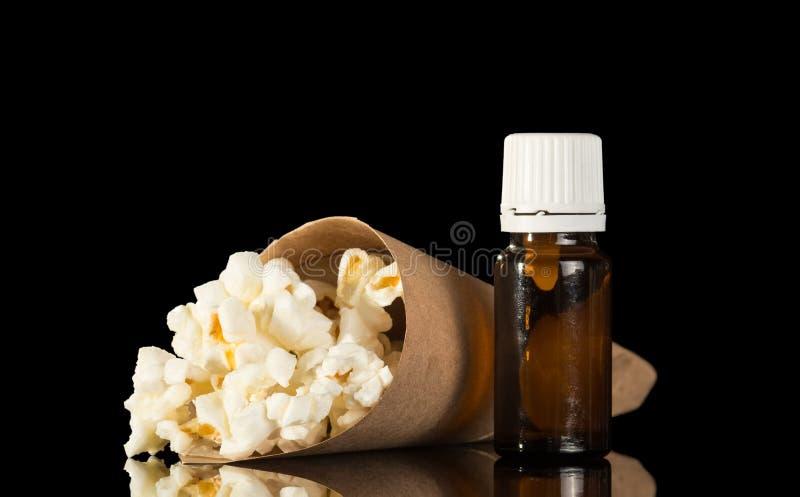 Flaska med doftande flytande för inhalation av ånga och av paketet med popcorn som isoleras på svart fotografering för bildbyråer