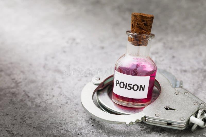 Flaska med gift och handfängsel på ett bord med kopieringsutrymme Straff för olaglig framställning av giftiga ämnen arkivbilder