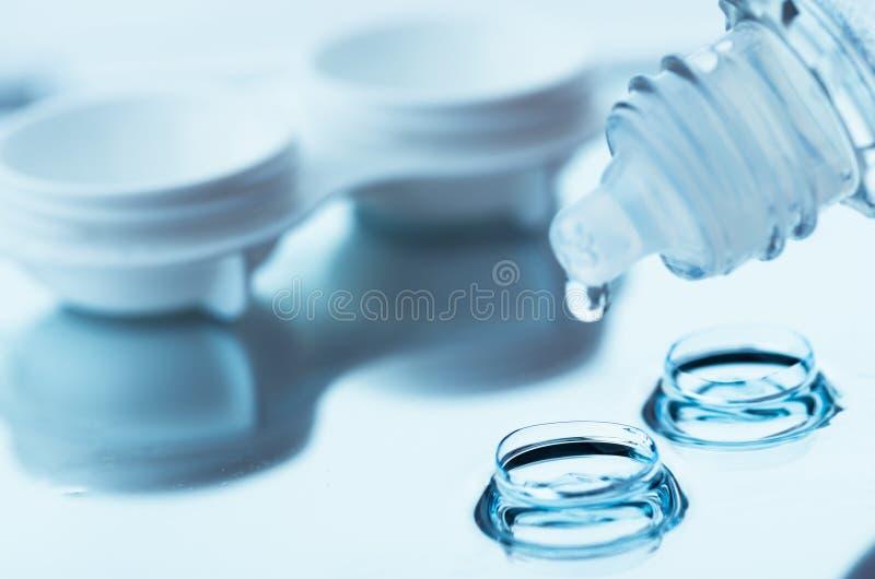 Flaska med linslösningen och fall på tabellen arkivbild