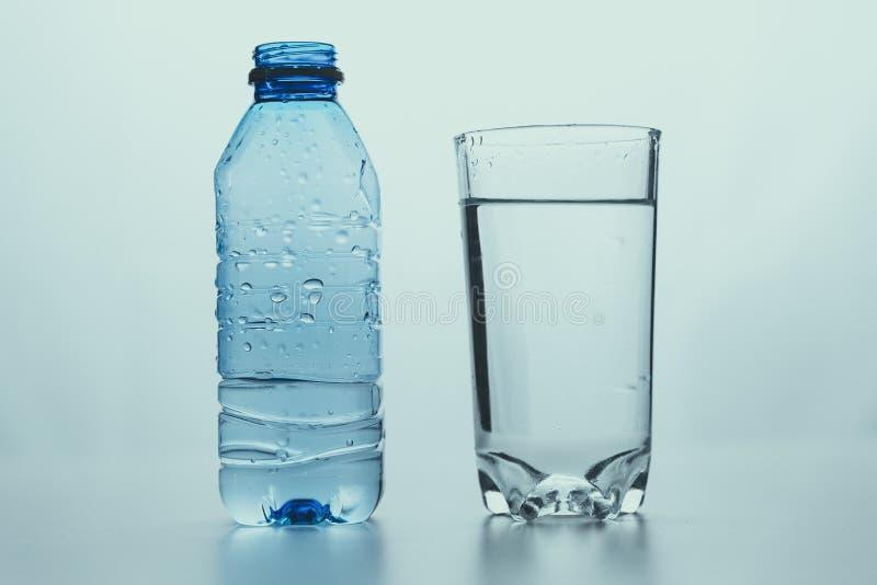 Flaska med vatten och ett glas rent vatten royaltyfria bilder