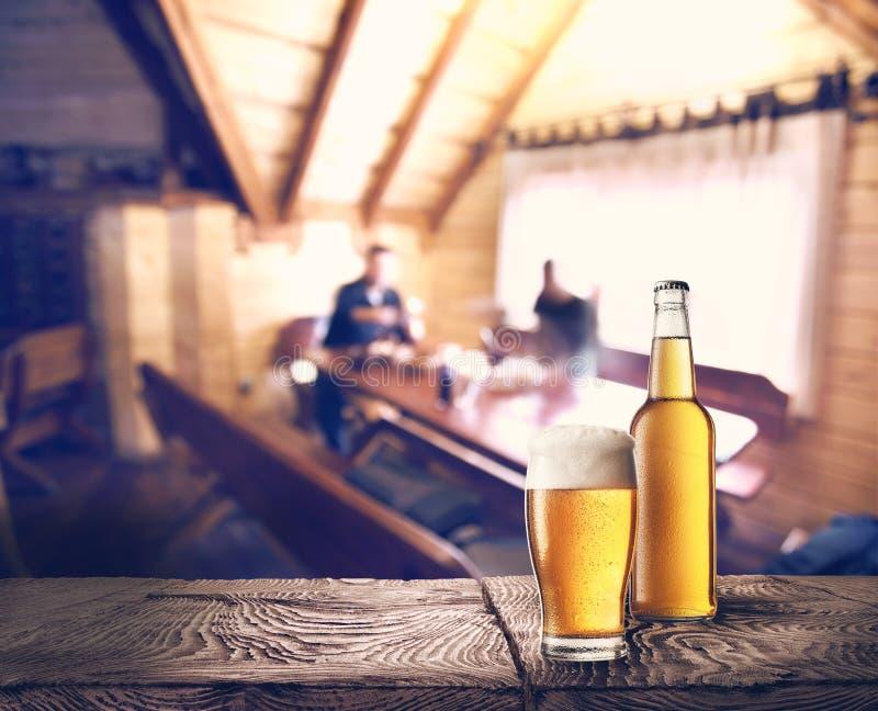 Flaska och exponeringsglas av öl på tabellen arkivfoton