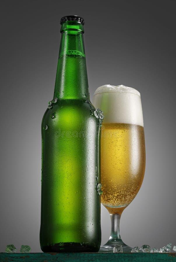Flaska och exponeringsglas av öl på trätabellen över grå backgroun royaltyfria bilder