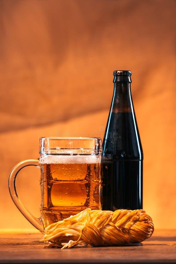 Flaska och exponeringsglas av nytt ljust öl med den rökte flätad tråden för ost på trätabellen royaltyfri foto