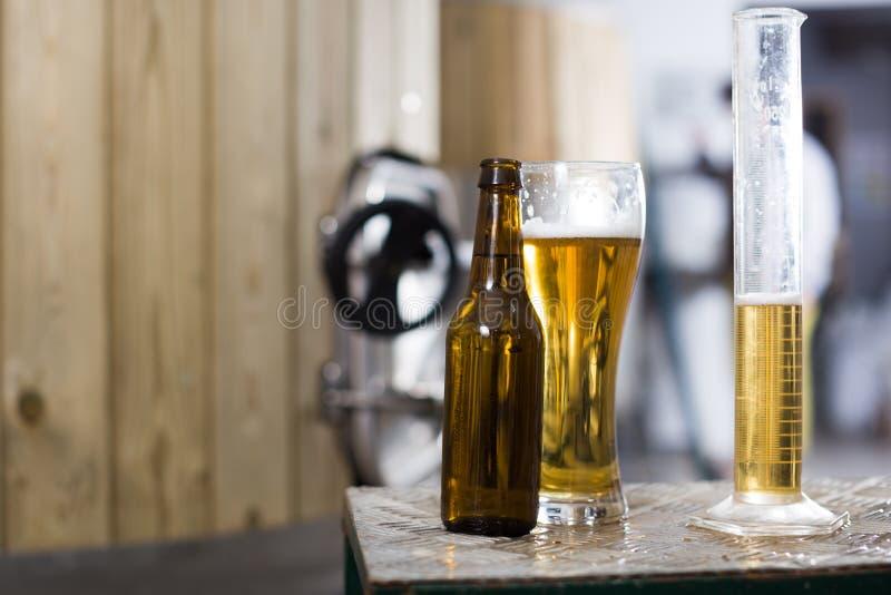 Flaska och exponeringsglas med guld- öl på bakgrunden av trummor för arkivfoto