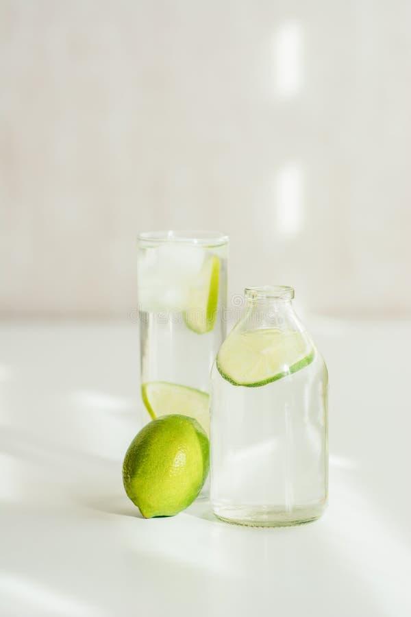 Flaska och exponeringsglas med vatten, is och limefrukt royaltyfria bilder