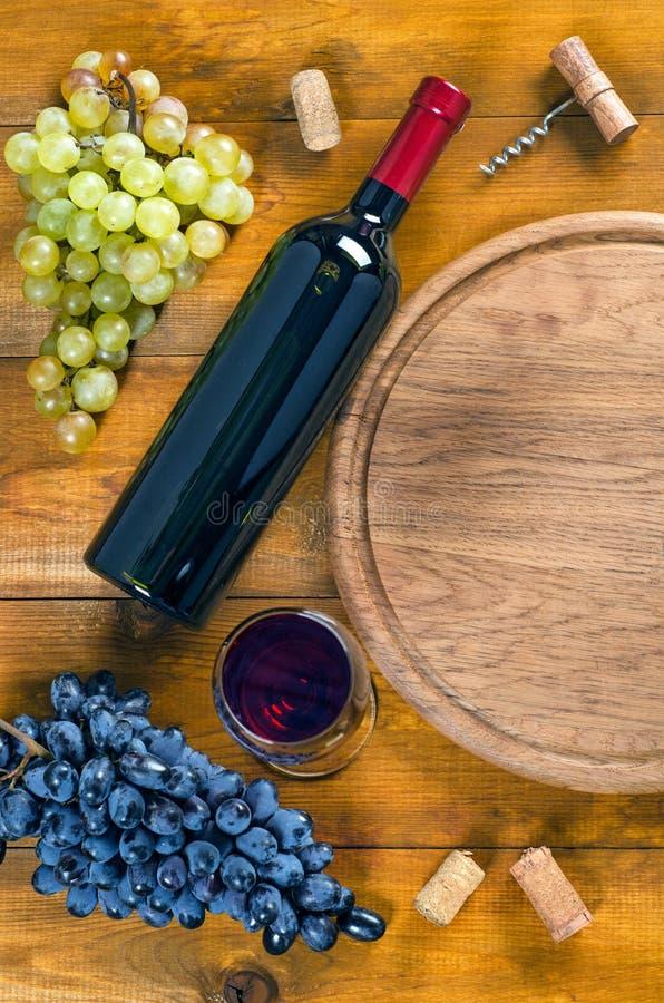 Flaska och exponeringsglas med vin, druvor, korkskruv, kork på trälodisar royaltyfria foton