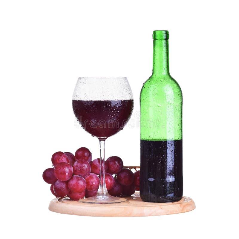 Flaska rött vin i exponeringsglas med druvor som isoleras på vit bakgrund arkivfoton