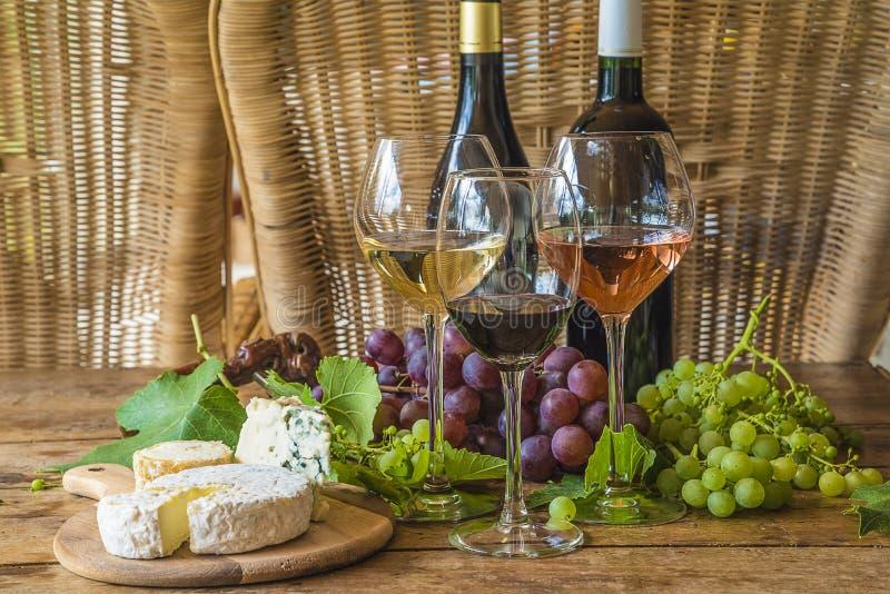 Flaska två av vin och tre exponeringsglas av vit, rosa färger och rött vin royaltyfri fotografi