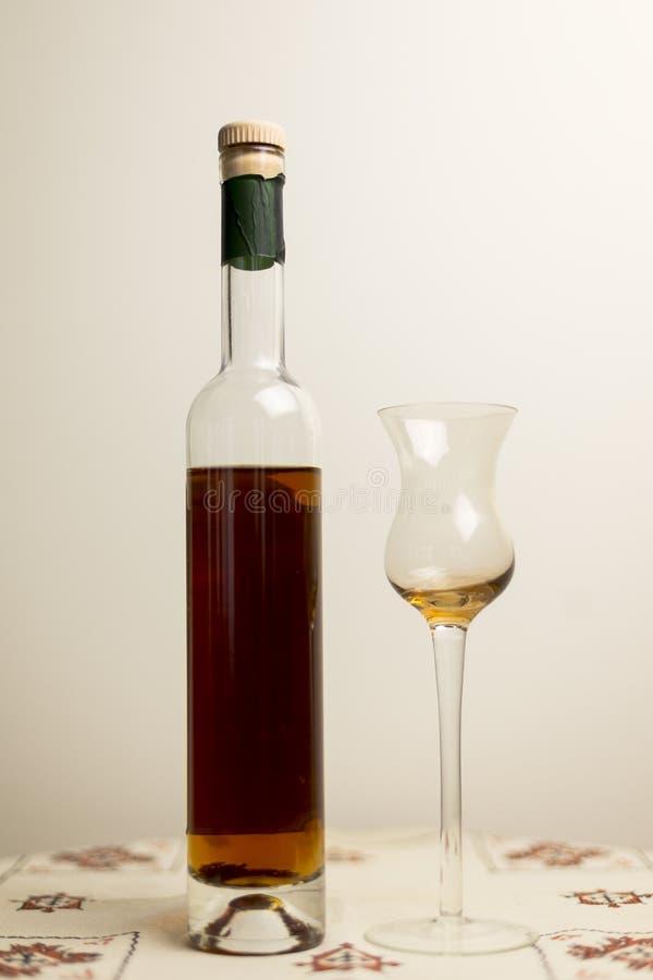 Flaskan av bärnsten färgat stärkt vin med tulpan formade innerligt exponeringsglas arkivbild