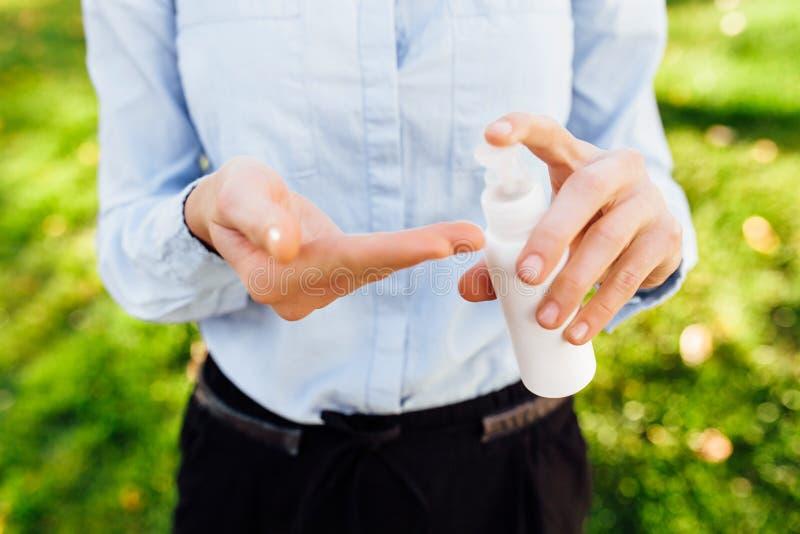 Flaskan av det antibacterial antiseptiska medlet stelnar i handen, bruk på gatan royaltyfria foton