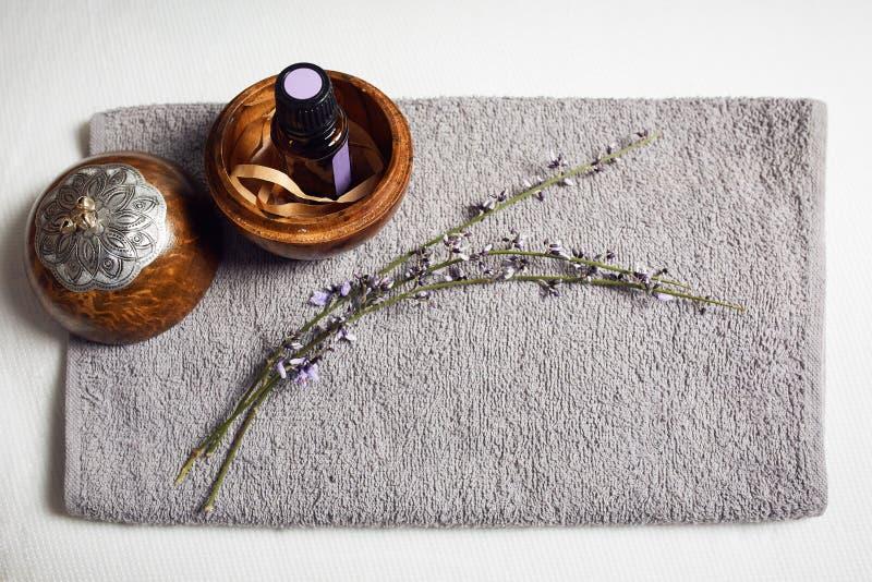 Flaskan av nödvändig olja i en rund bunke av trä, bredvid en lavendelfilial, båda ordnade på en grå rektangulär frottéhandduk arkivbild