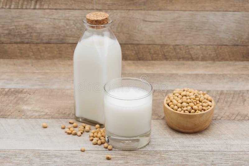 Flaskan av sojabönor mjölkar och sojabönan på trätabellen arkivfoto