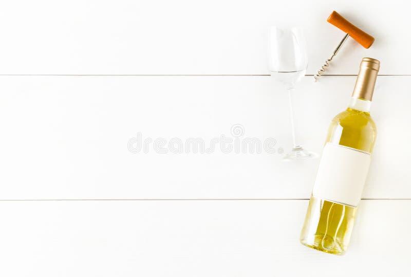 Flaskan för vitt vin med korkskruv- och vinexponeringsglas på den vita trätabellen lägger framlänges från över arkivfoton