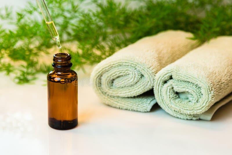 Flaskan med nödvändig olja, handdukar och gräsplaner på badrum kontrar arkivfoton