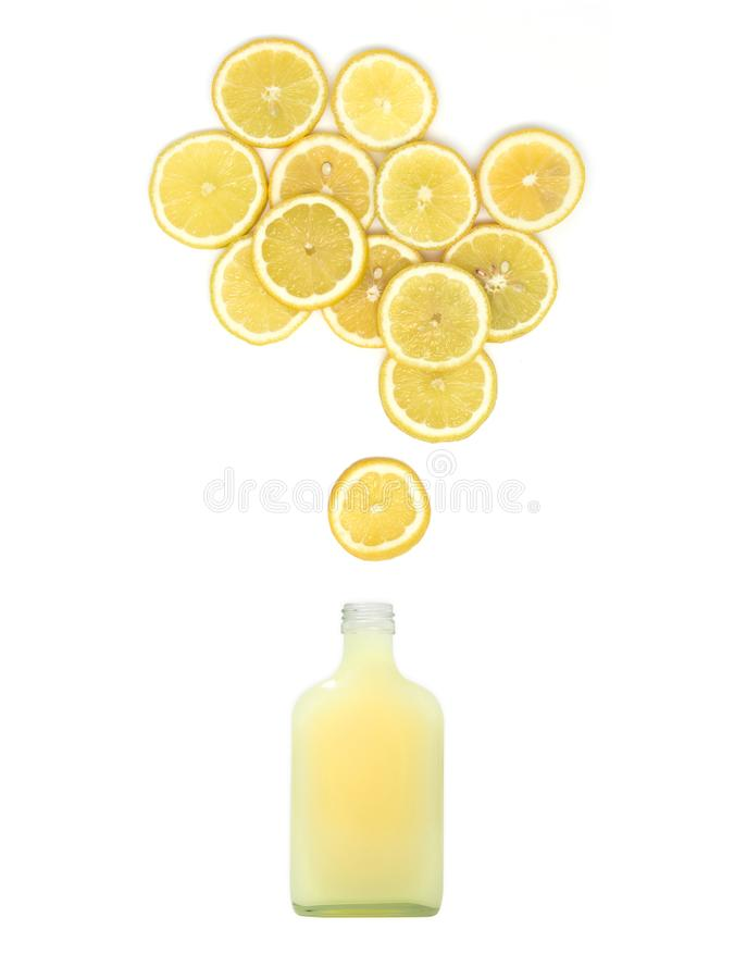 Flaskan med ny citronjuice står under många citronskivor på vit bakgrund royaltyfri foto