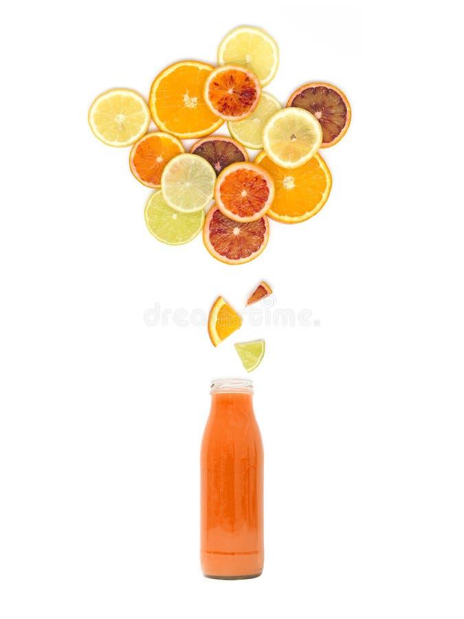 Flaskan med ny mång- citrus fruktsaft står under många apelsin-, citron-, limefrukt- och blodapelsinskivor på vit bakgrund arkivbilder