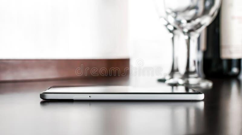 Flaskan med rött vin, två exponeringsglas och en mobiltelefon på brunt wodden tabellen på vit suddig väggbakgrund Alkoholdrink oc royaltyfria foton