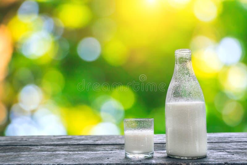Flaskan och exponeringsglas av förkylning mjölkar på trätabellen nya produkter för mejeri fotografering för bildbyråer