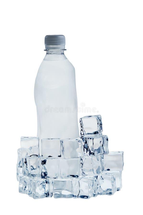 flaskan skära i tärningar is isolerat mineralvatten arkivbild