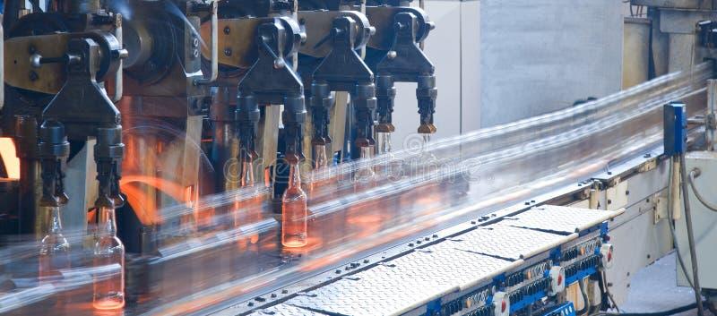Flaskfabrik, process av danandeglasflaskor arkivbild