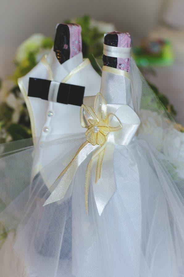Flaskor av champagne i en klänning av bruden och brudgummen arkivbilder