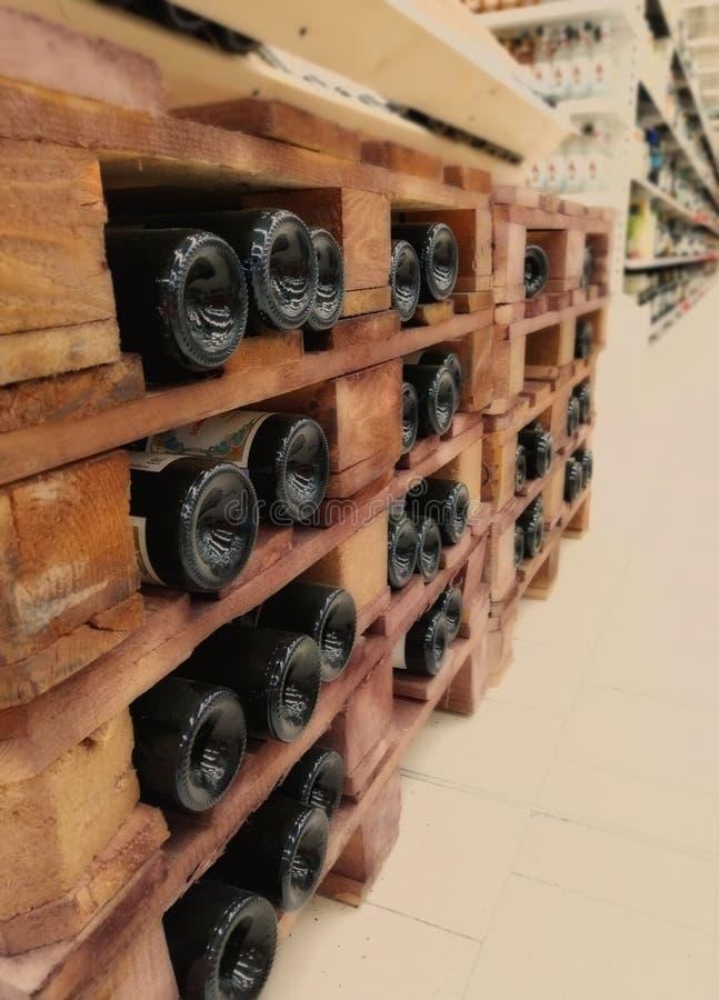 Flaskor av den bra dyra vinlögnen horisontellt på trähyllorna av källaren, i ett lager, i ett lager Tillgängligt för fotografering för bildbyråer