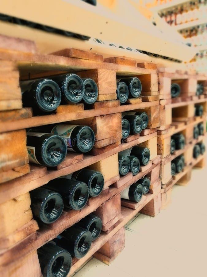 Flaskor av den bra dyra vinlögnen horisontellt på trähyllorna av källaren, i ett lager, i ett lager arkivfoton