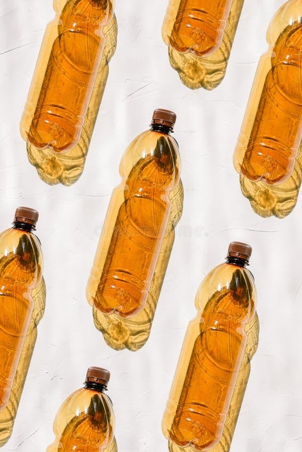 Flaskor av den bruna färglögnen på en vit bakgrund i rad Den ljusa solen skiner på kulör plast- som skapar en skugga från arkivbild