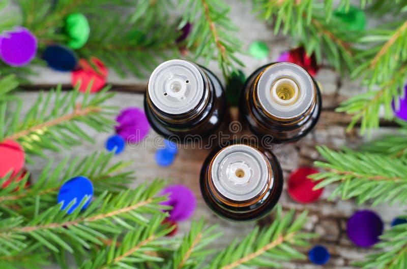 Flaskor av filialer för nödvändig olja och gran Jularomatherapy- och brunnsortbegrepp arkivbilder