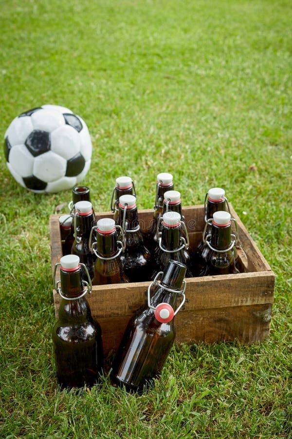 Flaskor av hantverköl eller lager med en fotbollboll royaltyfri fotografi