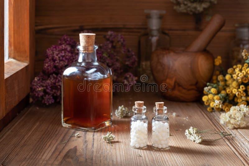Flaskor av homeopatiska piller med torkade örter arkivbild
