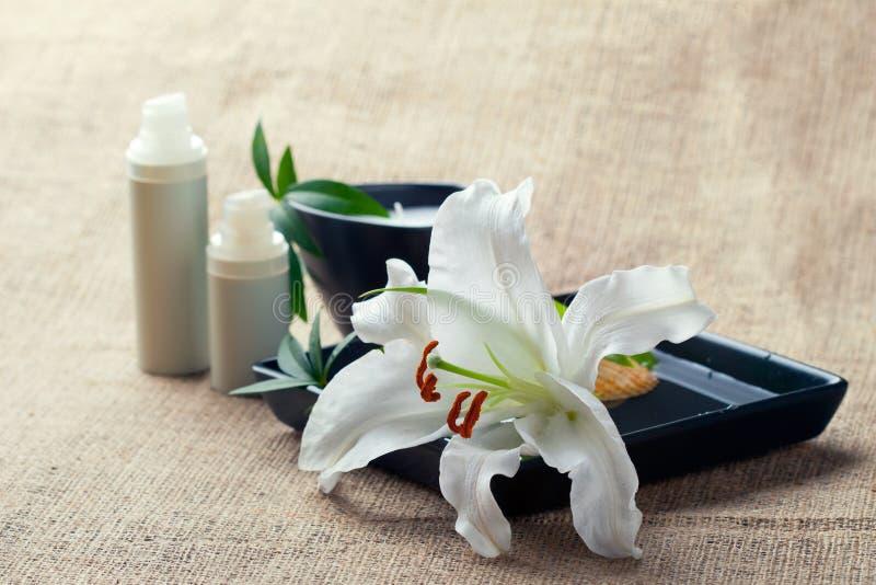 Flaskor av krämar/lotions med liljar royaltyfria foton