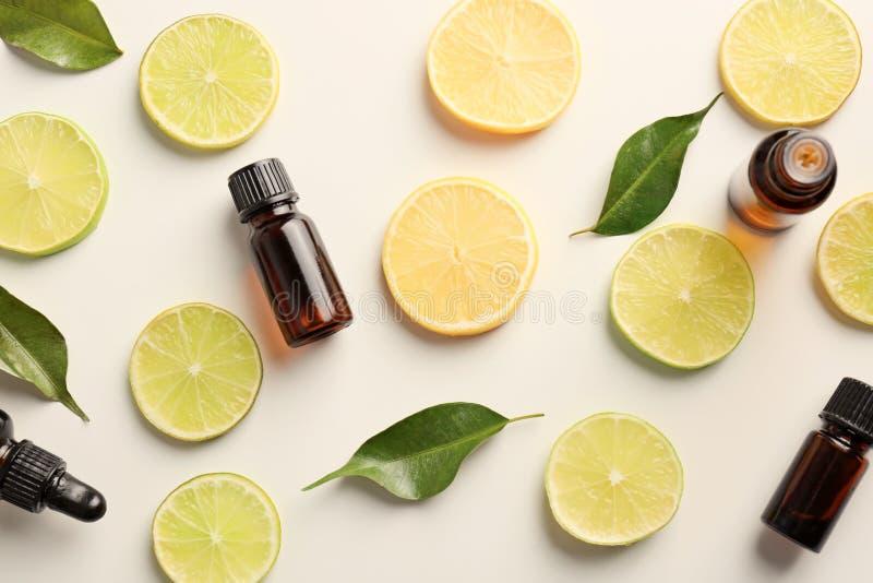 Flaskor av nödvändiga oljor och citrusa skivor på ljus bakgrund, bästa sikt royaltyfri foto