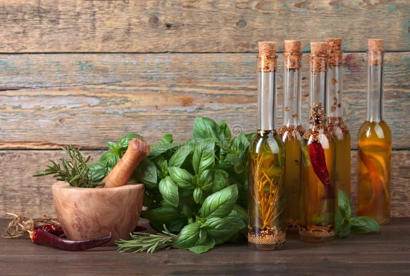 Flaskor av olivolja med basilika och trämortel royaltyfri bild