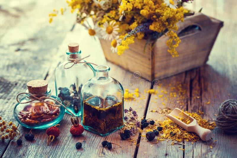 Flaskor av tinktur och torra sunda örter, blommaask royaltyfri fotografi