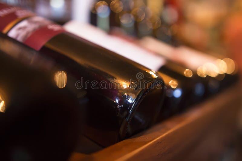 Flaskor av vin i rad i en närbild för vinlager royaltyfri fotografi