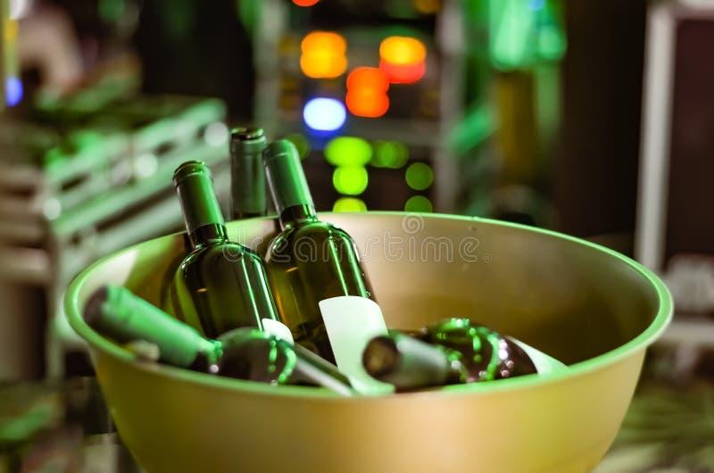 Flaskor av vin som är oöppnade i en guld- järnbunke för rostfritt stål på ett parti - händelse på en defocused klarteckenbakgrund royaltyfri bild