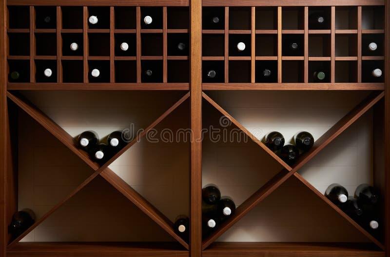 Flaskor av vit och rött vin på en trähylla med böcker i pr arkivfoto