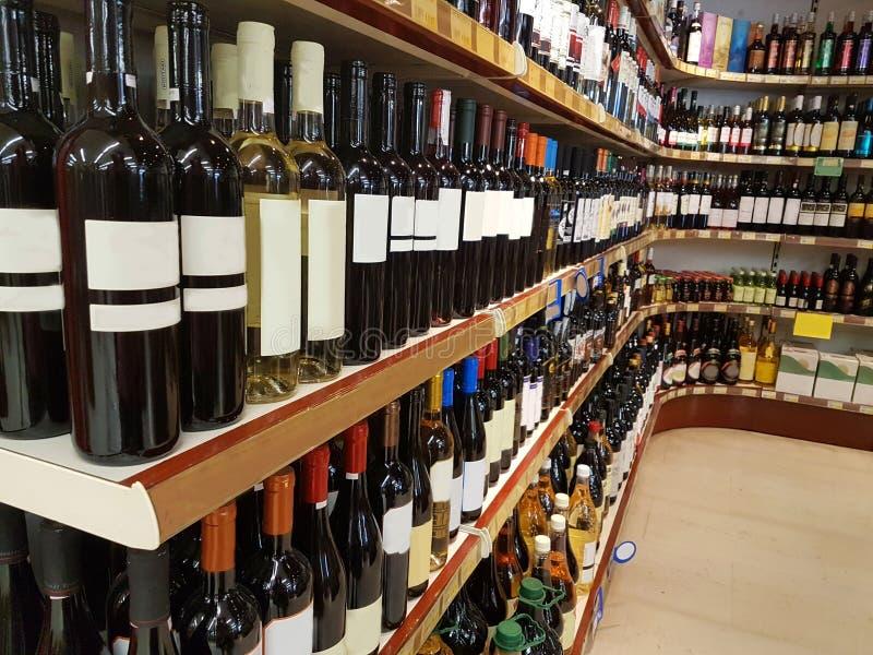 Flaskor för drinkar för vinlager på hylla royaltyfri foto