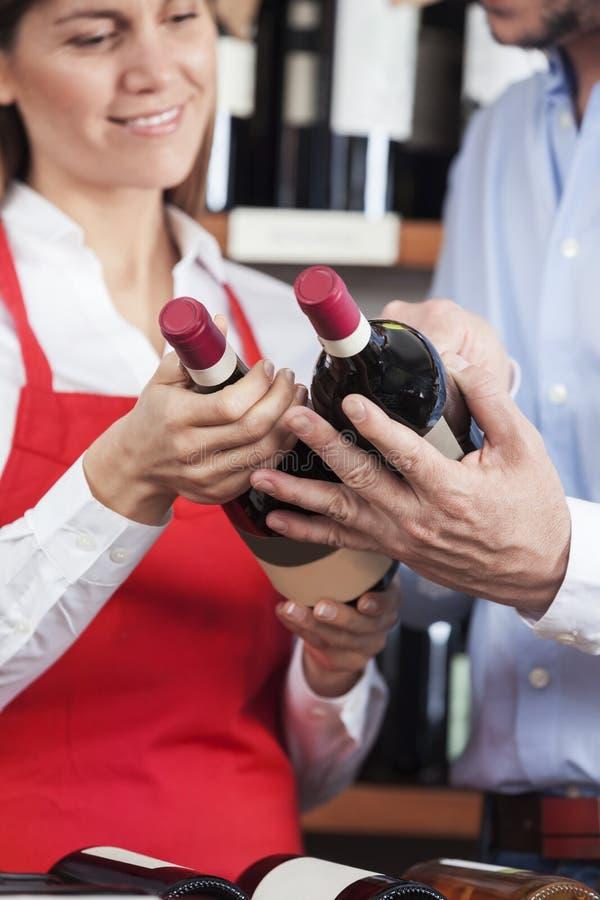 Flaskor för försäljareAnd Male Customer hållande vin royaltyfri foto