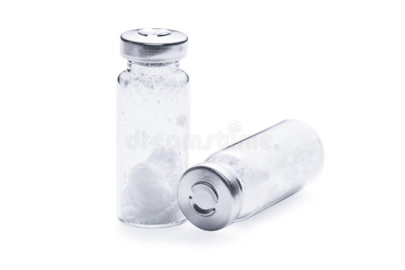 Flaskor för injektion med vitt pulver på en vit bakgrund arkivfoto
