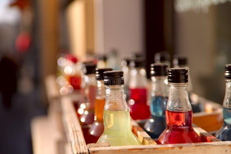 Flaskor i en tr?ask som fylls med kul?ra drinkar arkivfoto