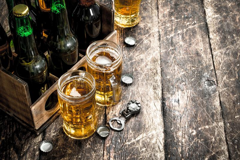 Flaskor med öl i en gammal ask arkivfoto