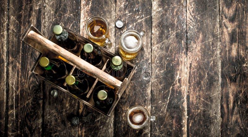 Flaskor med öl i en gammal ask arkivfoton