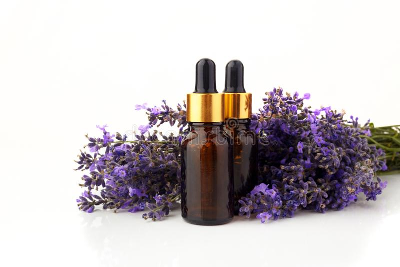 Flaskor med aromolja- och lavendelblommor som isoleras på vit arkivfoton
