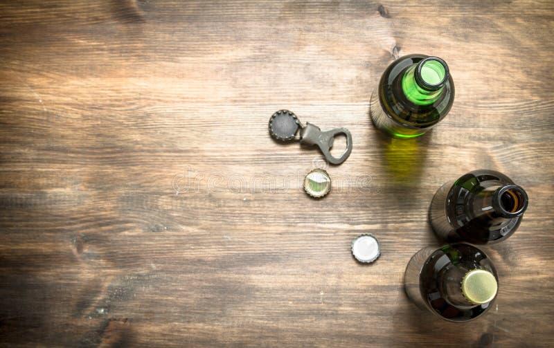 Flaskor med den nya öl, öppnaren och proppar arkivbild