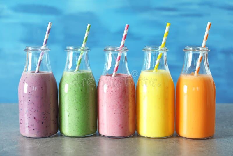 Flaskor med den smaskiga smoothien på tabellen mot bakgrund royaltyfria foton